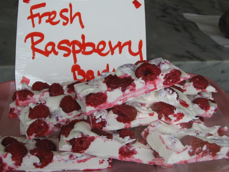 white chocolate with fresh raspberries with a sign that reads 'fresh raspberry bark'