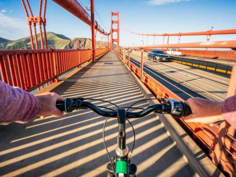 a person's hands on a set of bicycle handlebars on an empty walkway on the golden gate bridge