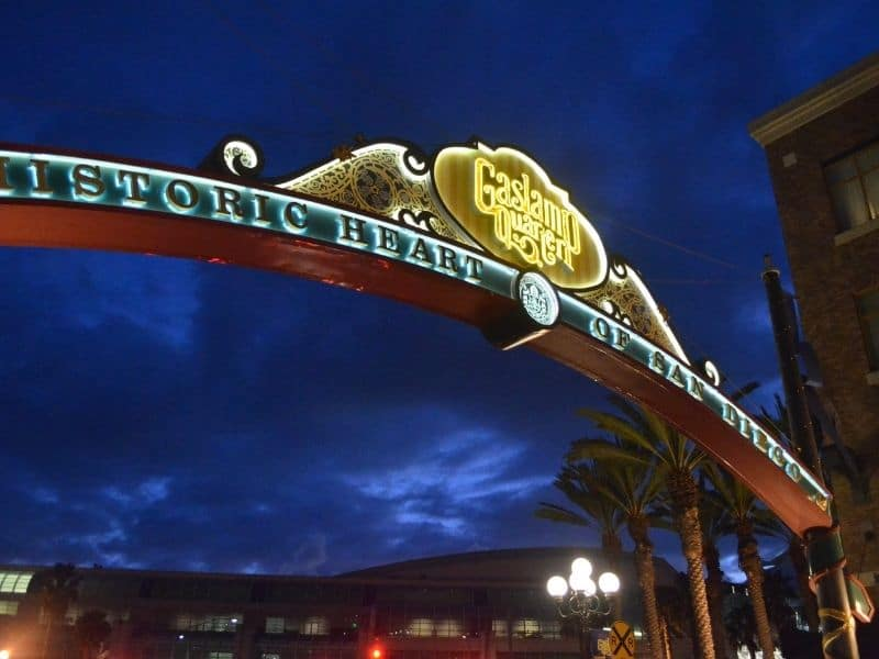 the archway entrance to the gaslamp quarter lit up at night with lights