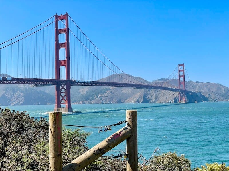 view of the water below the golden gate bridge and the red spans of the suspension bridge and hills behind it