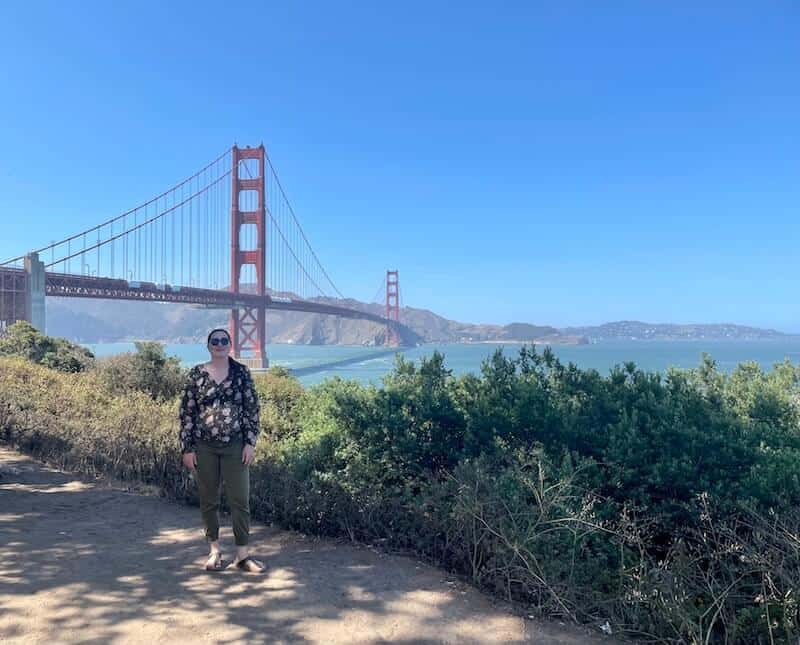 Allison standing with a view of the Golden Gate Bridge behind her and shrubbery on a trail walking to the bridge