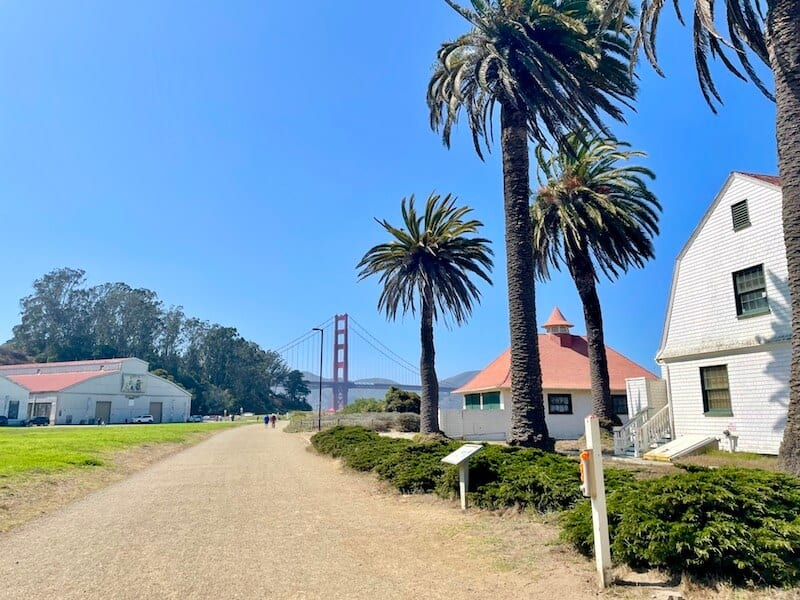 walking down the scenic crissy field promenade with palm trees and old military buildings with a view of the golden gate off in the distance at the end of the path