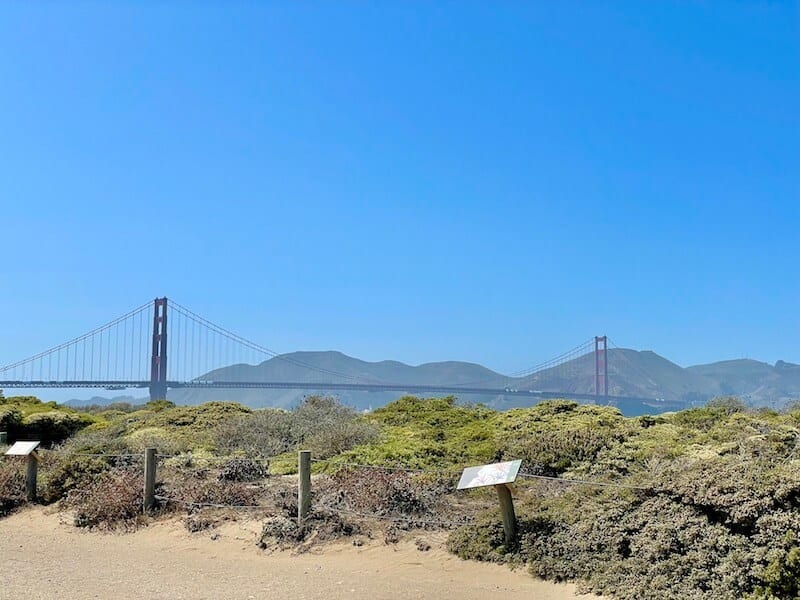 The Golden Gate Bridge on a blissfully sunny day near Crissy Field with trail and views