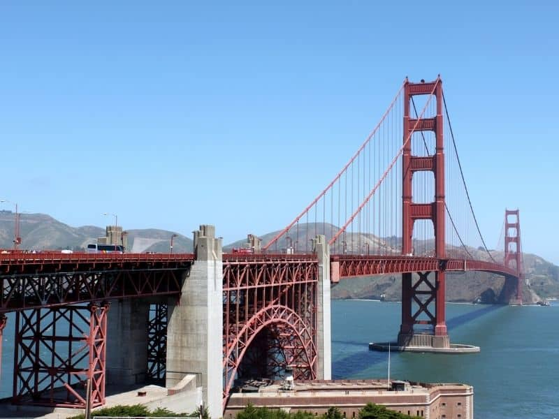 seeing the arch and the span of the golden gate bridge with its two red towers crossing over the blue waters of the bay