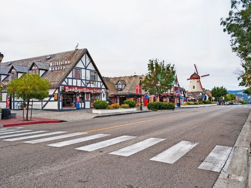 a crosswalk in the charming danish-style village of solvang california with its famous windmill visible down the street