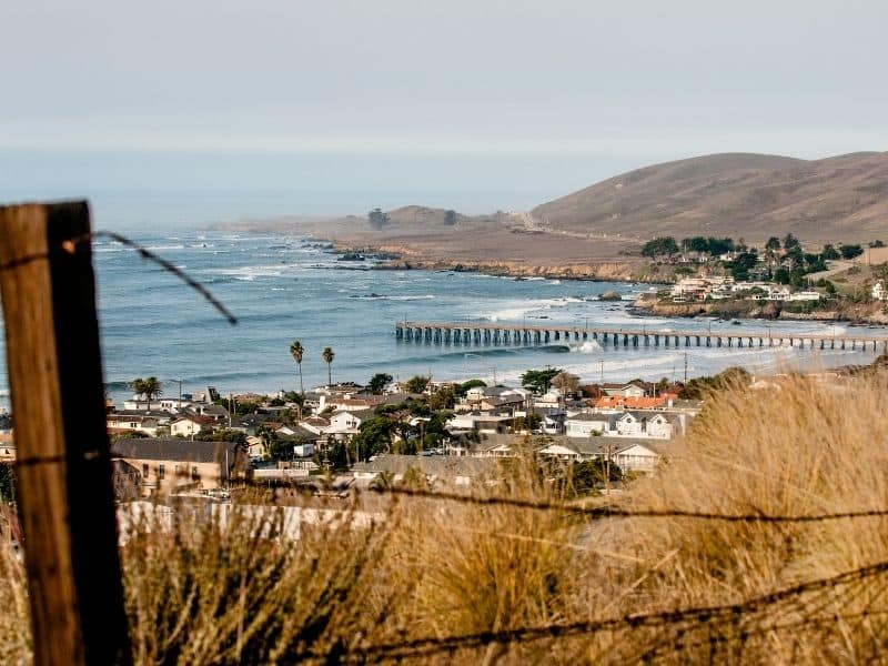 the town of cayucos seen from a hill above the town with the historic pier and beach visible