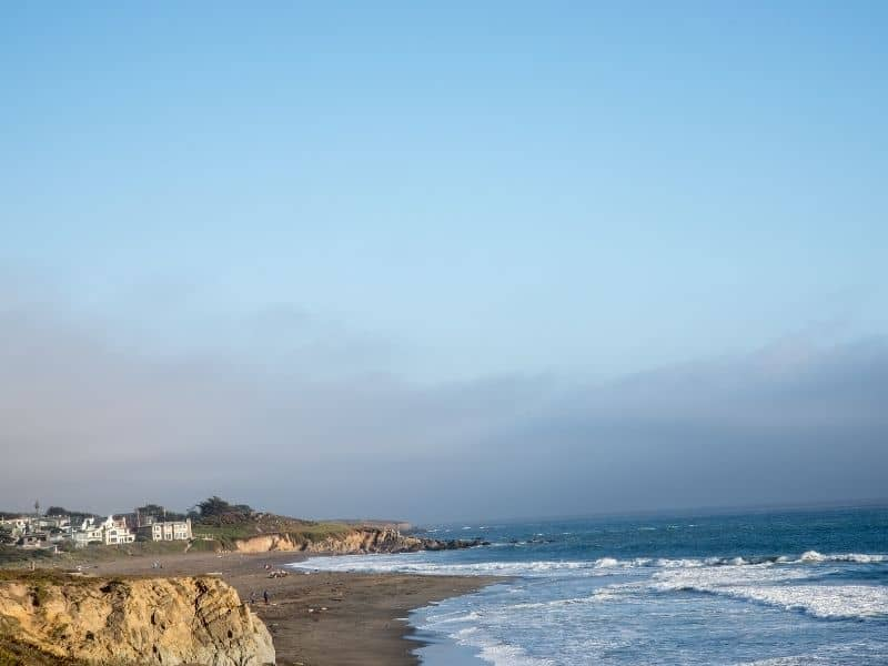 the coastline of cambria with some beach houses visible in the distance as waves lap the central coast shoreline on this drive from los angeles to big sur