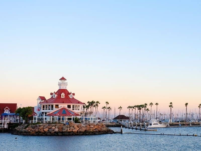 the beautiful harbor lighthouse with marina and palm trees at sunset colors