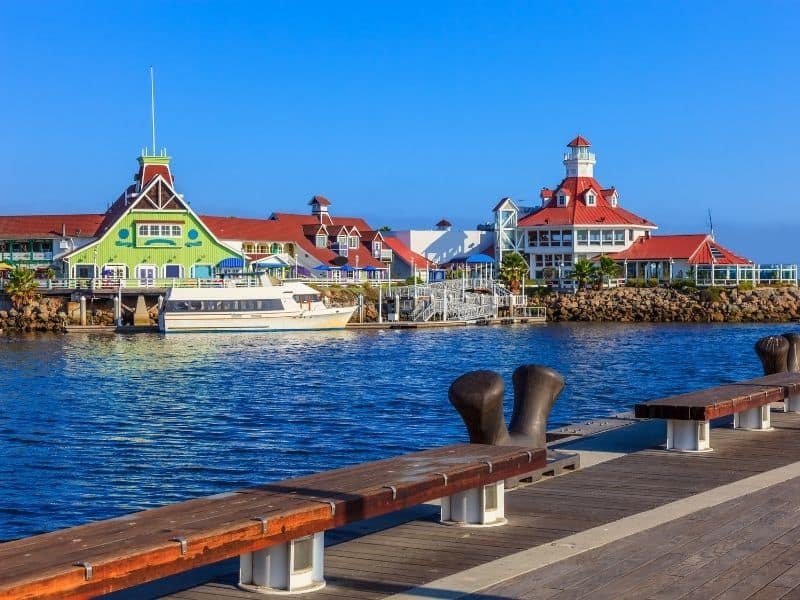 view of the lighthouse and other iconic buildings from the rainbow harbor area of long beach california