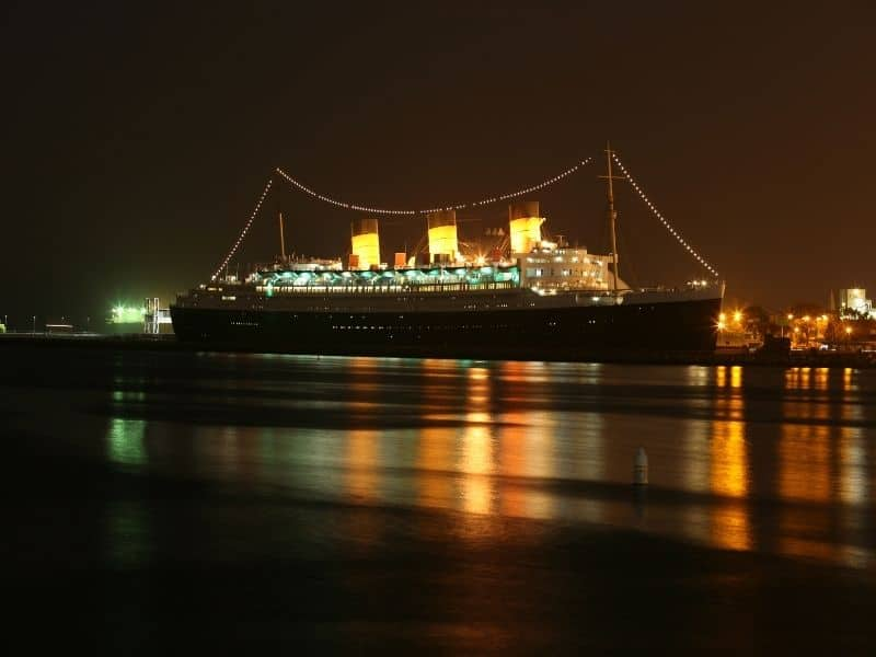 boat lit up with lights at night and water lit up as well
