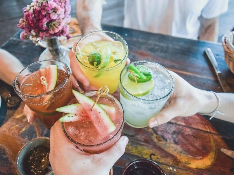 four hands cheerings with different flavored margaritas including lime and watermelon