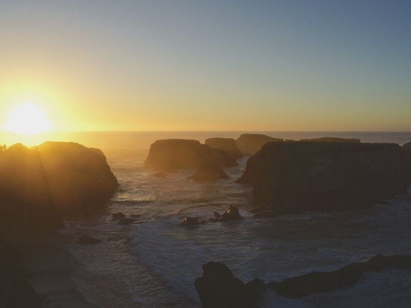 watching the sun set over the rock formations of Mendocino beach