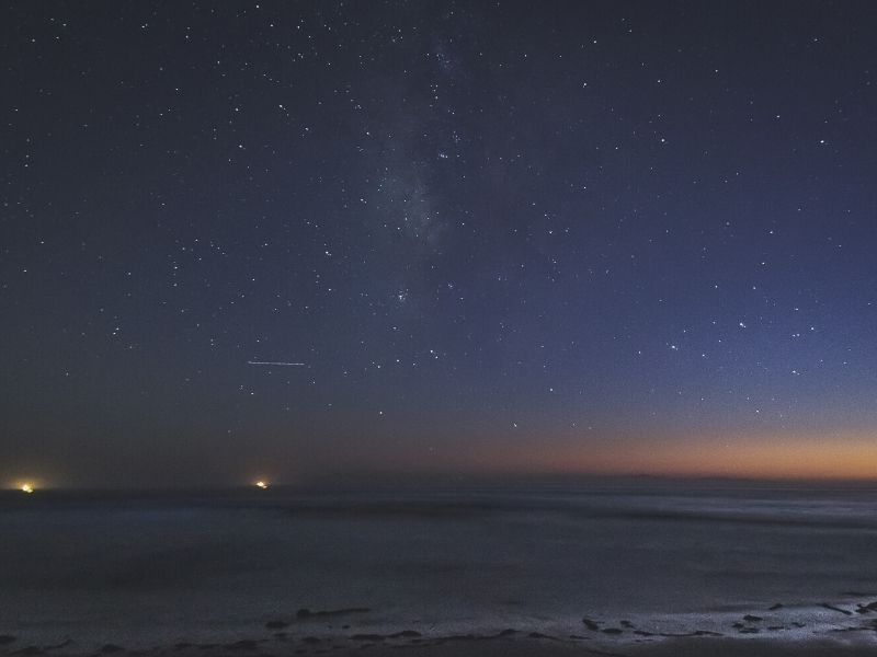 stars over the pacific ocean and lights from ships off the coast