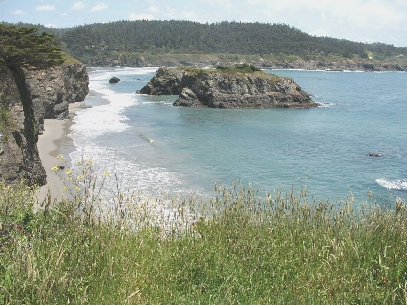 walking on the grassy hills in mendocino headlands state park above the rocky outcroppings in the ocean below