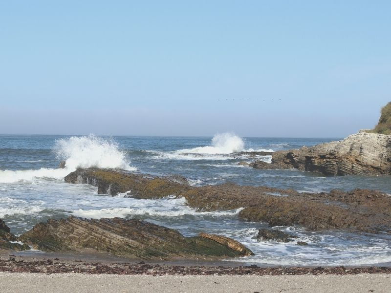 waves crashing on rocks in the ocean at spooners cove in Montana de oro state park near morro bay