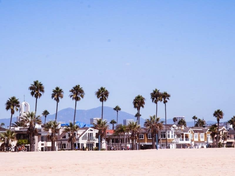 the beach at newport beach with houses, palm trees and a mountain behind in the distance