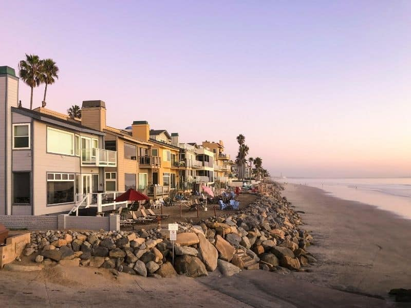 beach houses on the shore of oceanside with a pinkish purple sunset in the distance