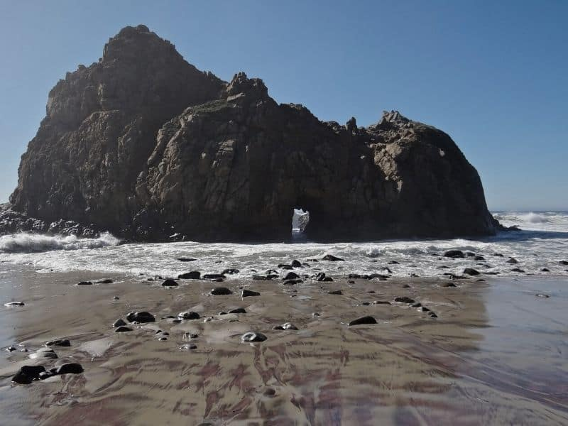 pfeiffer beach and rock formation with a small arch in it