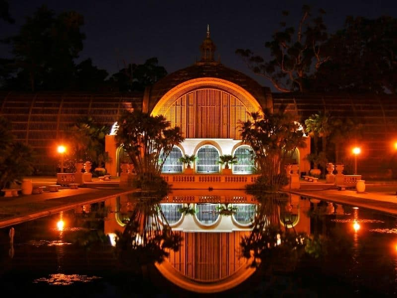 botanical garden building in bright red lights reflecting on a still pool at night