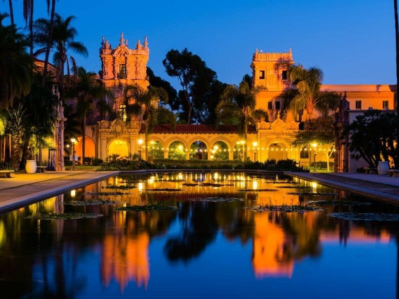 balboa park pond lit up at night in bright colors with dark blue sky