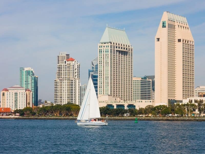 sailboat in the water in front of san diego skyline buildings ascending in height from left to right