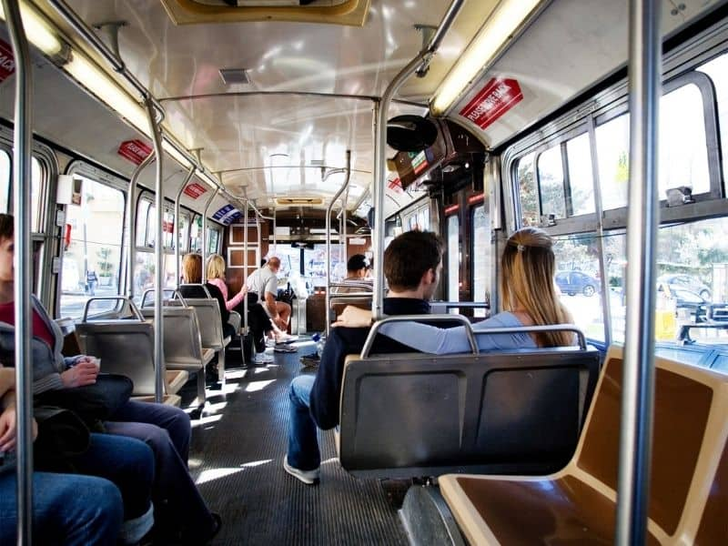 taking public transit in san francisco inside of a bus with people inside