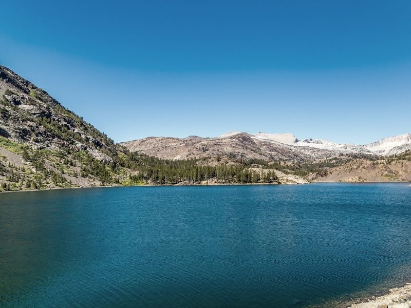 flat, turquoise water at ellery lake in tioga pass on the road over the mountains