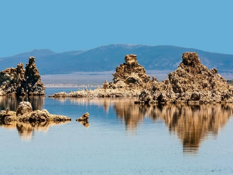 tufa rock formations of mono lake reflected in the water