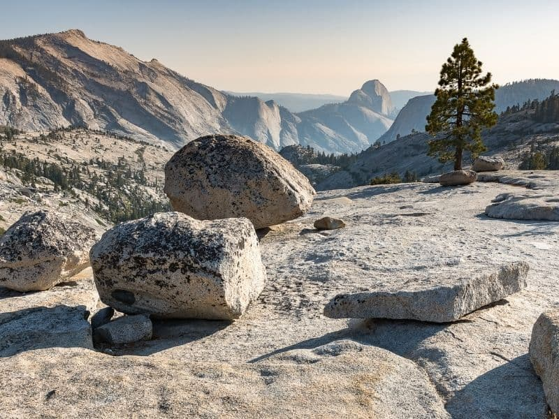 views close up of rocks along olmsted point with views of half dome and clouds rest in the distance