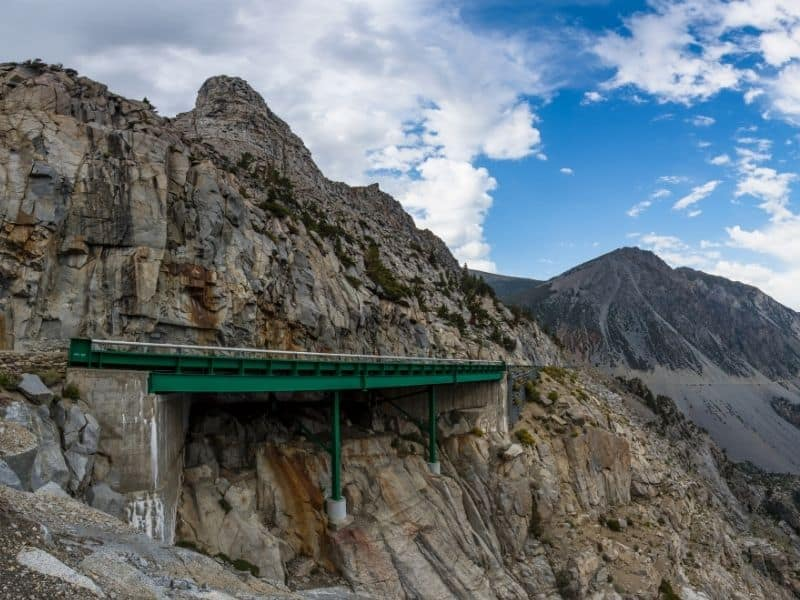 a view of the mountain road of tioga pass from afar where you can see the engineering of a green bridge into the craggy mountainous area