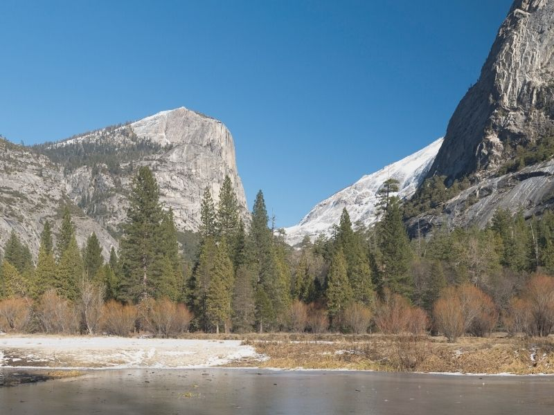 the frosted-over waters of mirror lake with half dome in the background
