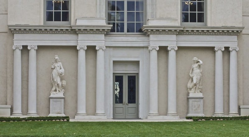 front of a tan building with white pillars and two sculptures on either side of a door