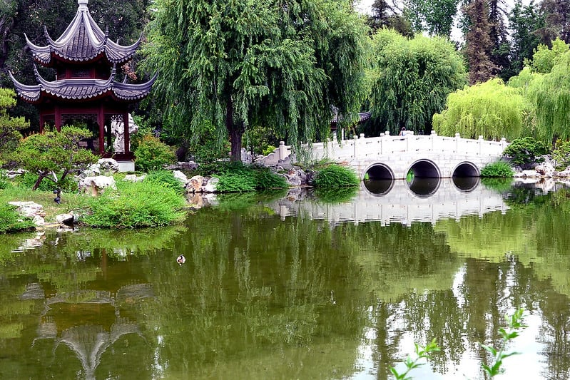 white bridge reflected into a pond and a two-tiered pagoda also reflected in a green chinese-inspired pond