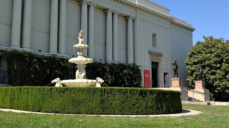 fountain, hedge, and white building with pillars at the huntingon library. andgardens