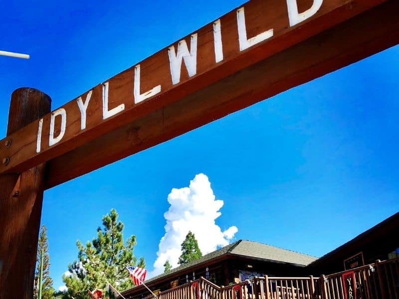 sign that reads idyllwild in front of a wooden lodge