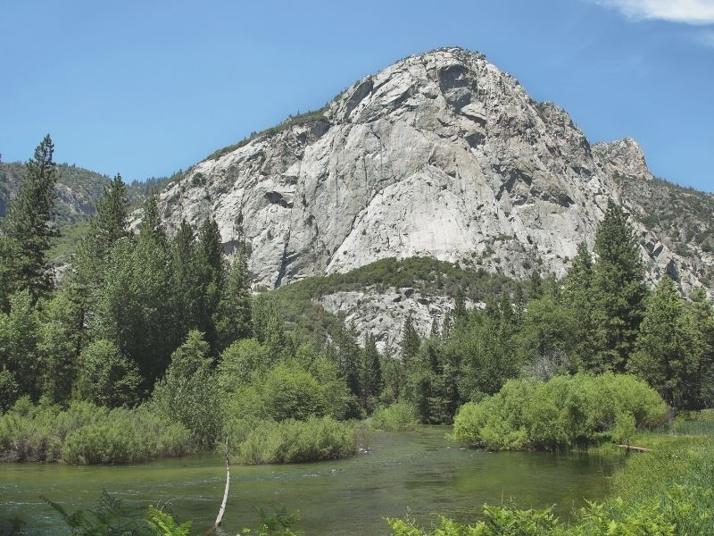 photo of a river surrounded by greenery and trees and a granite dome at kings canyon national park california
