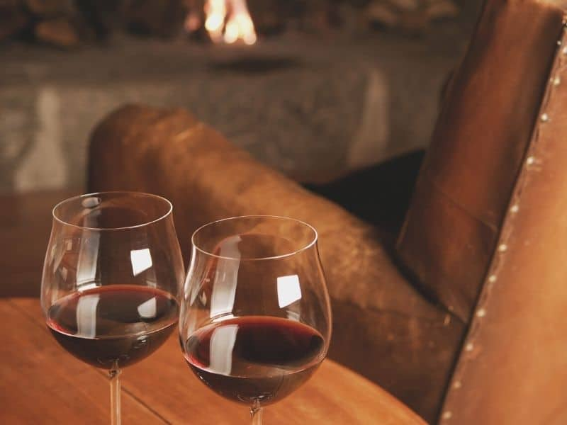 two glasses of cabernet sauvignon red wine on a table next to a leather armchair with a fire in the background in napa in winter