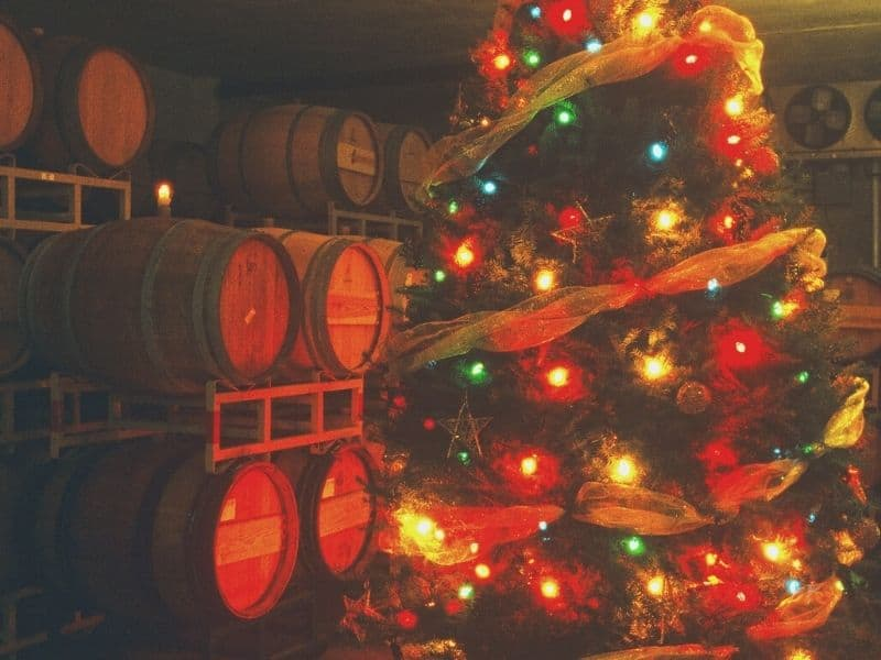 wine barrels and a christmas tree lit up and decorated