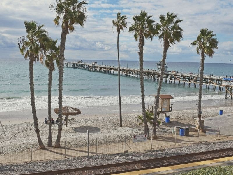 train tracks in front of the beach and long wooden pier in southern California with palm trees