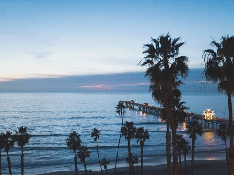 san clemente pier at night shortly after sunset at blue hour with palm trees and blue water
